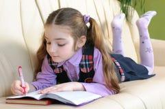 Het meisje dat van de school homeworks doet Stock Afbeelding
