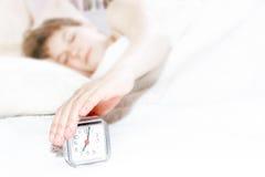 Het meisje dat van de slaap de wekker probeert uit te zetten Stock Afbeelding