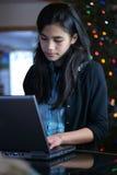 Het meisje dat van de tiener aan laptop werkt Stock Foto's
