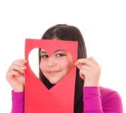Het meisje dat van de tiener door een hart gestalte gegeven knipsel kijkt Stock Afbeeldingen