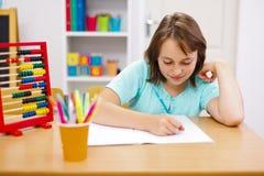 Het meisje dat van de tiener en thuiswerk uitoefent doet Stock Foto's