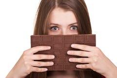 Het meisje dat van de tiener grote chocoladereep houdt Stock Foto's