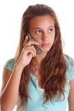 Het meisje dat van de tiener op celtelefoon luistert Stock Foto