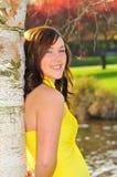Het meisje dat van de tiener op een berkboom leunt stock foto