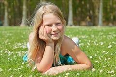 Het meisje dat van de tiener op gras ligt royalty-vrije stock afbeeldingen