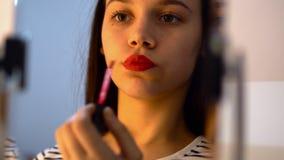 Het meisje dat van de tiener rode lippenstift zet stock foto