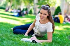 Het meisje dat van de tiener rollerskates met boek draagt Stock Afbeelding