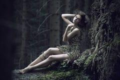 Het meisje dat van Eco op de boomstam ligt stock afbeelding