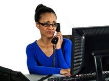 Het meisje dat van het bureau aan een computer werkt Stock Foto's