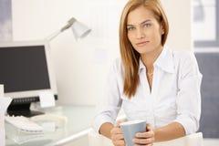 Het meisje dat van het bureau van koffiepauze geniet Stock Foto