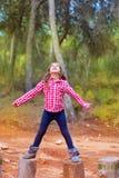 Het meisje dat van het jonge geitje boomboomstammen met open wapens beklimt Stock Foto