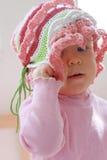 Het meisje dat van het jonge geitje haar hoed verwijdert Stock Afbeelding