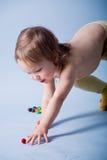 Het meisje dat van het jonge geitje kleine bal bereikt Stock Afbeeldingen