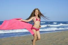 Het meisje dat van het strand roze handdoek en wind speelt stock afbeelding