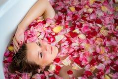 Het meisje in de badkamers met roze bloemblaadjes, sluit omhoog portret royalty-vrije stock foto