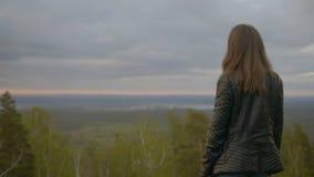 Het meisje in de bergen bekijkt de hemel stock video