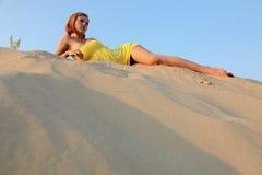 Het meisje in de blauwe hemel ligt op zand stock fotografie
