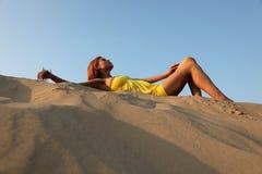 Het meisje in de blauwe hemel ligt op zand stock afbeeldingen
