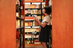 Het meisje is in de boekhandel of de bibliotheek royalty-vrije stock fotografie