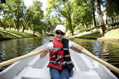 Het meisje in de boot op roeispanen op het kanaal Stock Foto