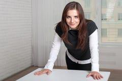 Het meisje in de bureautribunes propped haar handen op de lijst stock foto's