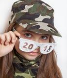 Het meisje in de camouflagehoed en grappige glazen met de inschrijving 2018 Royalty-vrije Stock Afbeeldingen