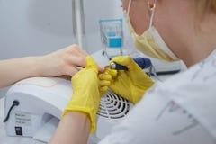 Het meisje in de dienst van de salonspijker Groepering van spijkers en behandeling van spijkers met een elektrische machine nT stock afbeelding