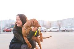 Het meisje is de eigenaar en de hond op de achtergrond van de stad bij zonsondergang Dood met een hond in de stad tijdens de zons stock afbeelding