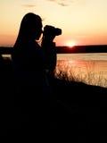 Het meisje de fotograaf tegen een zonsondergang stock foto