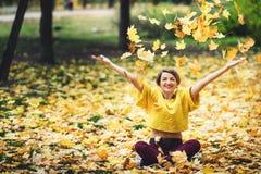 Het meisje in de herfst zit op gras en giet cheerfully omhoog gele bladeren Zie mijn andere werken in portefeuille stock foto