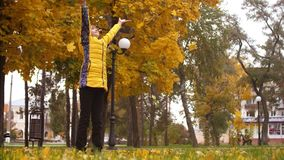 Het meisje in de herfstpark werpt op gele bladeren van de esdoorn Langzame Motie stock footage