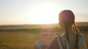 Het meisje in de hoed en de kleding is op het gebied bij zonsondergang stock videobeelden