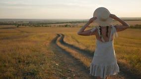 Het meisje in de hoed en de kleding is op het gebied bij zonsondergang stock footage