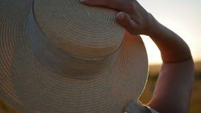 Het meisje in de hoed en de kleding is op het gebied bij zonsondergang stock video