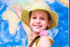 Het meisje in de hoed glimlacht en toont de wereldkaart stock fotografie