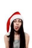Het meisje in de hoed van de Kerstman zette uit zijn tong Stock Fotografie