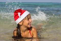 Het meisje in de hoed van Santa Claus zwemt Stock Foto