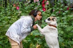 Het meisje in de hoofdtelefoons en de glazen naast de hond pooch op de achtergrond van bloemen Latino meisje van verschijning met stock foto's