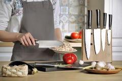 Het meisje in de keuken met mes Stock Afbeelding