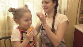 Het meisje in de keuken met mijn mamma eet een gele peper stock footage