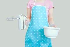 Het meisje in de keukenschort houdt een mixer en een kom Grijze achtergrond stock afbeelding