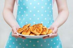 Het meisje in de keukenschort houdt een witte plaat met koekjes in haar handen stock afbeeldingen