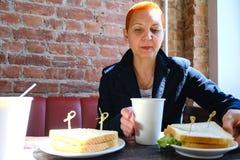 Het meisje in de koffie die een latte drinken die een sandwich eten Het loensen in het zonlicht De zon van het venster glanst op  stock fotografie