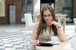 Het meisje in de koffie die een tablet lezen Royalty-vrije Stock Foto