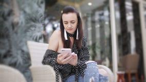 Het meisje in de koffie gebruikt een smartphone stock videobeelden