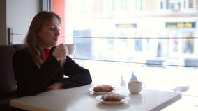 Het meisje in de koffie het drinken thee stock videobeelden