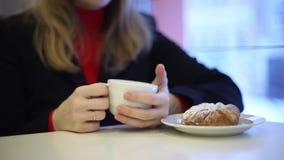 Het meisje in de koffie het drinken thee stock footage