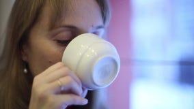 Het meisje in de koffie het drinken thee stock video