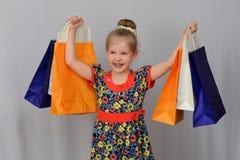 Het meisje, de koper houdt de gekleurde het winkelen zakken Royalty-vrije Stock Afbeeldingen