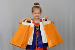 Het meisje, de koper houdt de gekleurde het winkelen zakken Stock Afbeeldingen